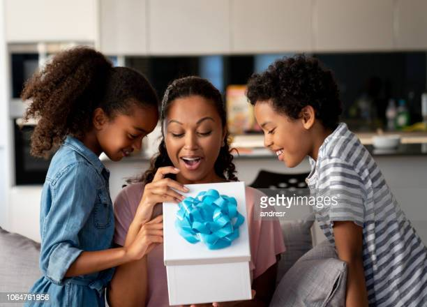 happy kids surprising their mother with a gift for mother's day - happy mothers day stock pictures, royalty-free photos & images