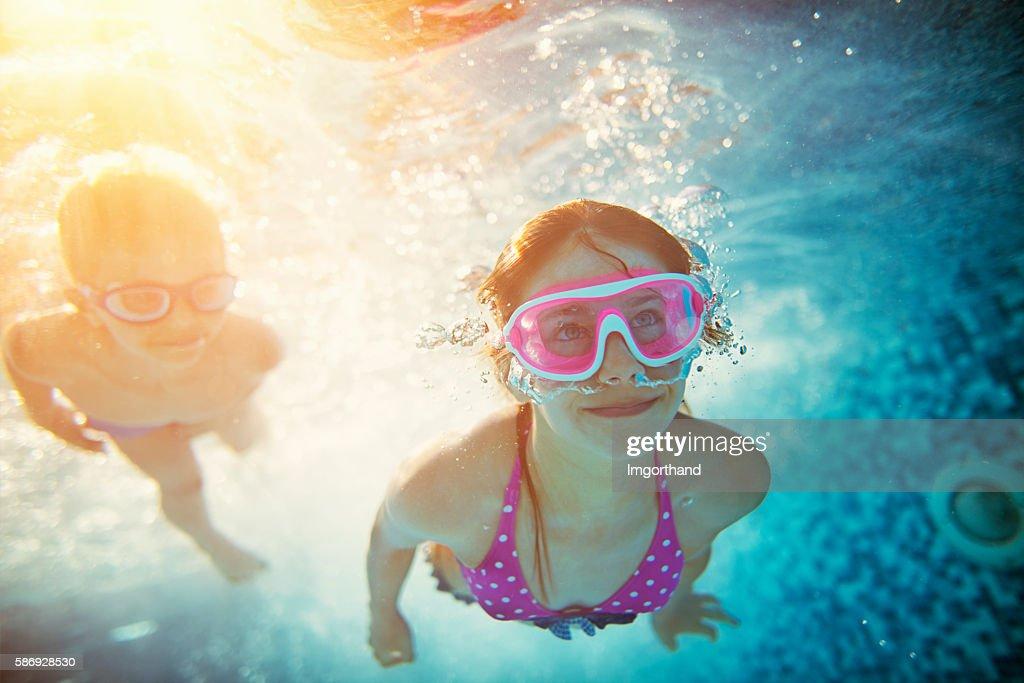 Happy kids swimming underwater in pool : Stock Photo