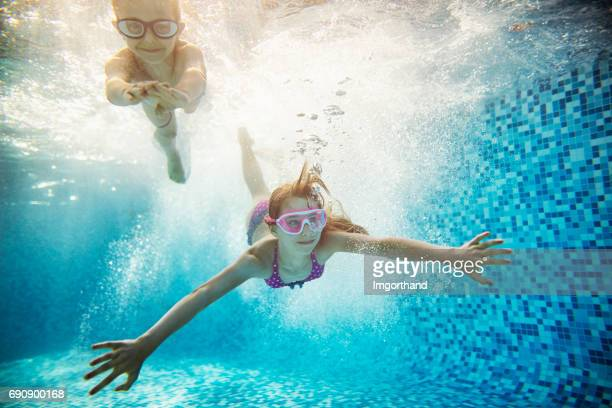 happy kids swimming underwater - imgorthand stock photos and pictures
