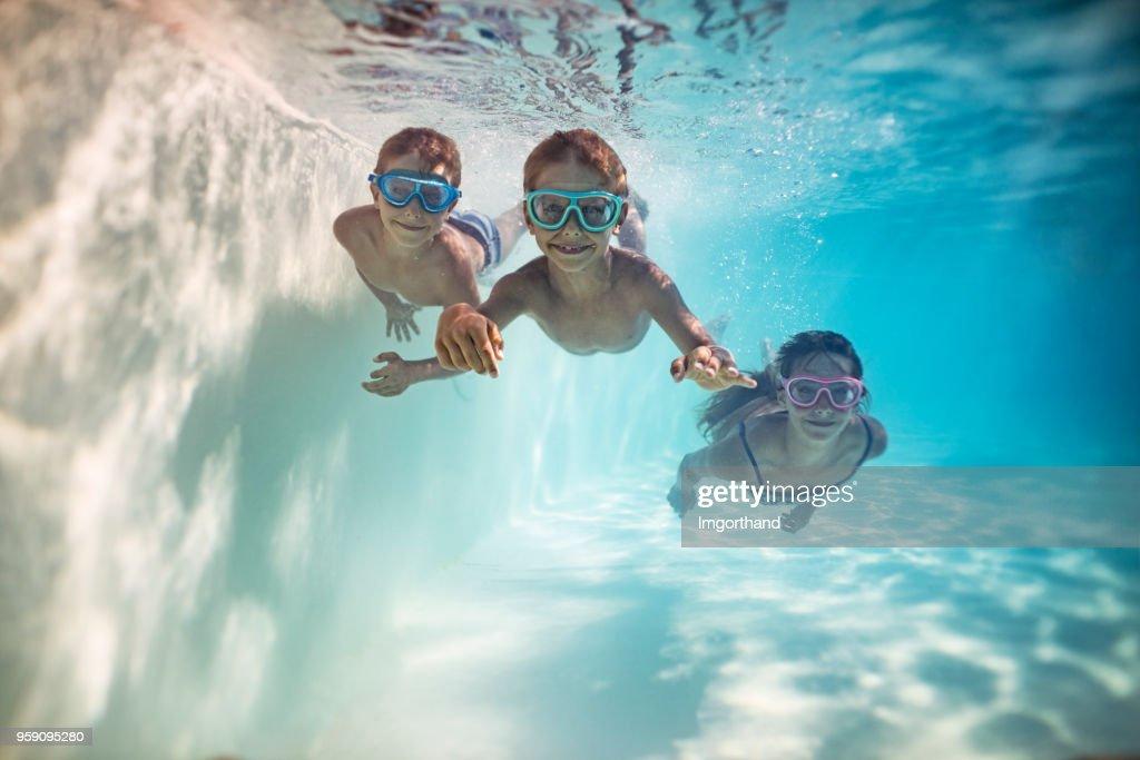 Happy kids swimming underwater : Stock Photo