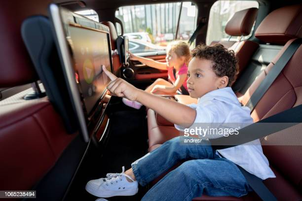 happy kids watching television in a car while wearing their seat belt fastened - fastening stock pictures, royalty-free photos & images