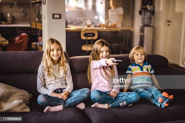 happy kids tv kijken op sofa in de woonkamer. - televisie kijken stockfoto's en -beelden