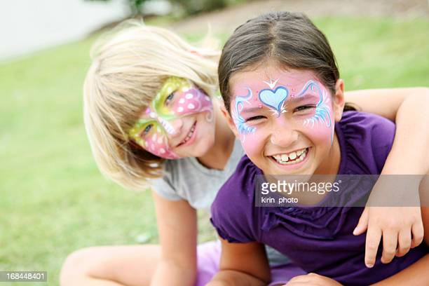 Happy kids with painted faces wearing purple