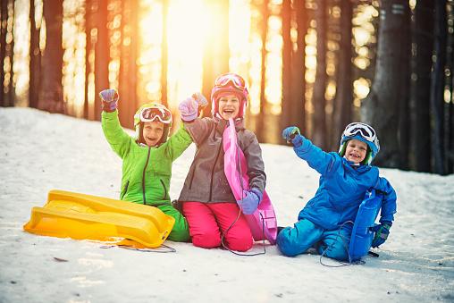 Happy kids with toboggans enjoying winter 615744384