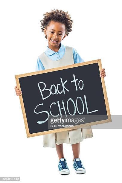 happy kindergarten girl in uniform holding back to school sign - beautiful ethiopian girls stock photos and pictures