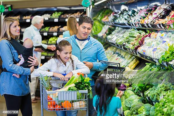 Happy large family shopping together in supermarket