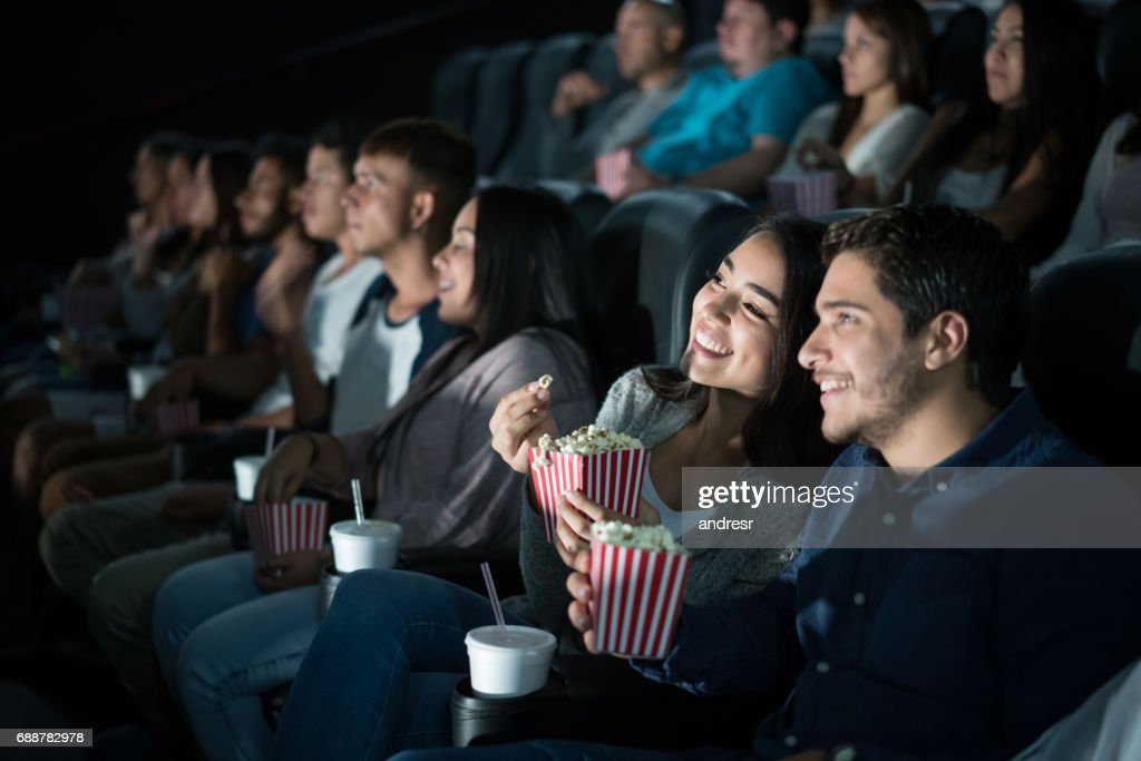 Happy Latin American couple at the movies : Stock Photo