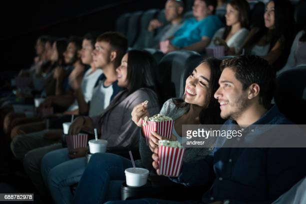 happy latin american couple at the movies - industria cinematografica foto e immagini stock