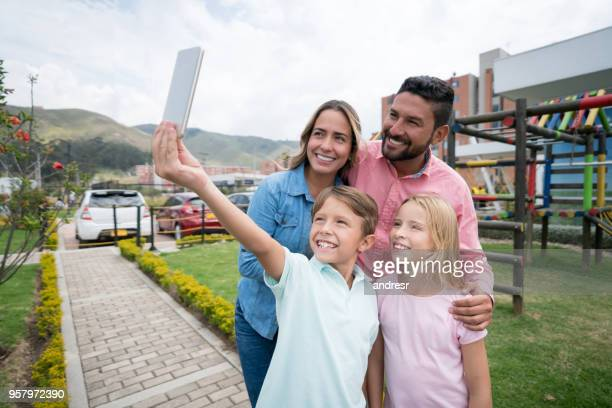happy latin american family at a building complex and little boy taking a selfie all looking at camera smiling - beautiful wife pics stock pictures, royalty-free photos & images