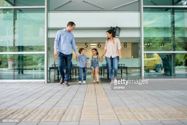 Happy Latin American family exiting the hospital