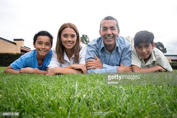 Happy Latin American family lying outdoors