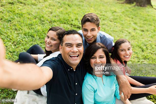 Happy latin familly taking a selfie outdoors