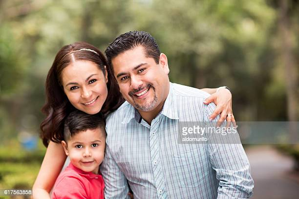 Happy latin family with one child smiling at camera