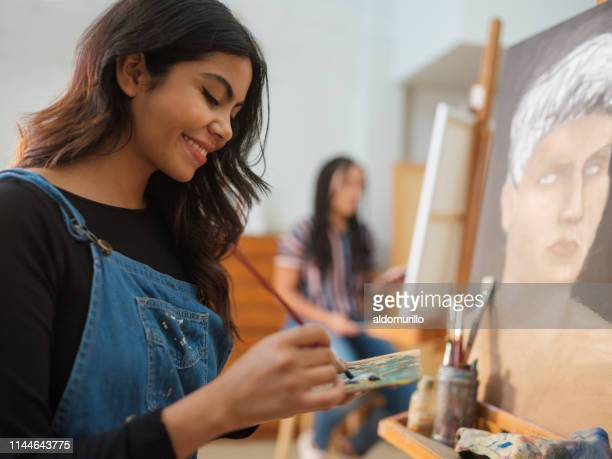 happy latin female working on a painting - art stock pictures, royalty-free photos & images