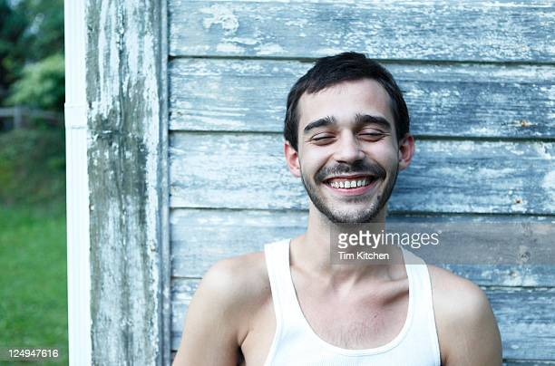 Happy Latin guy laughing near shed outdoors