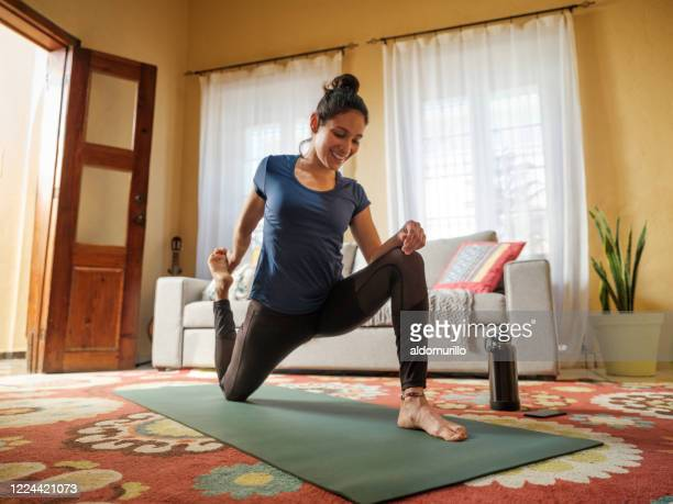 happy latin woman stretching legs on mat in living room - mental wellbeing stock pictures, royalty-free photos & images