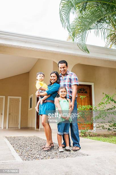Happy Latino family outside their home