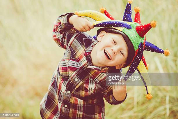 happy laughing boy playing & wearing joker hat outdoors - joker card stock photos and pictures