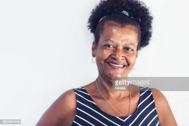 Happy laughing brazilian woman in front of white wall