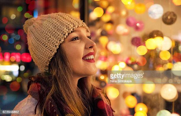 Happy laughing girl looking at Christmas lights, profile