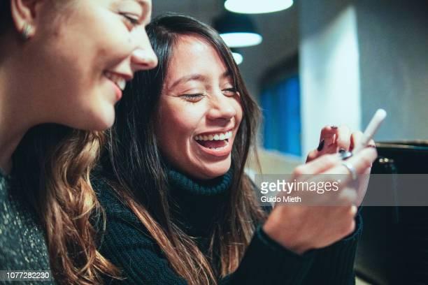 Happy laughing girlfriends having a coffee break.
