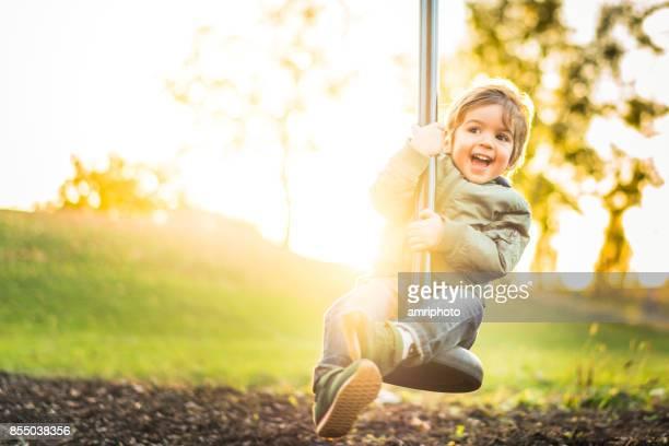 glücklich lachende kleiner junge auf seilrutsche bei strahlendem sonnenschein - kinderspielplatz stock-fotos und bilder