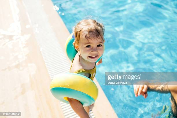 happy laughing toddler girl having fun in a swimming pool - uv protection stock pictures, royalty-free photos & images