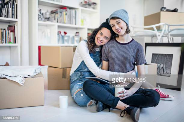 Happy lesbian couple embracing by cardboard boxes