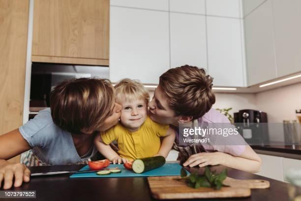 happy lesbian couple kissing their child in kitchen - lesbica imagens e fotografias de stock