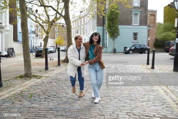 happy lesbian couple laughing while walking together on footpath - couple relationship stock pictures, royalty-free photos & images