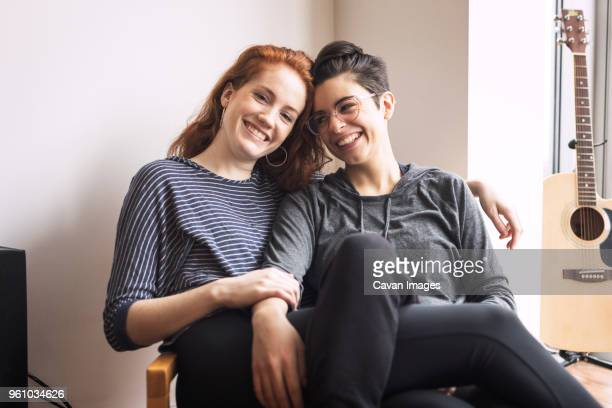 happy lesbian couple sitting on chair at home - lesbiana fotografías e imágenes de stock