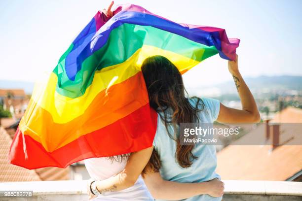 happy lesbian couple waving lgbt flag outdoors - gay rights stock photos and pictures