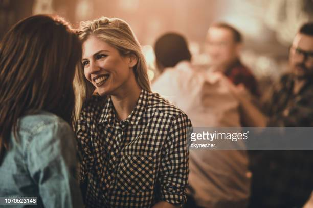 happy lesbian woman flirting with her friend in a pub. - lesbian dating stock pictures, royalty-free photos & images