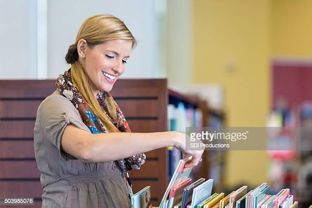 Happy librarian sorting childrens books on rolling library cart