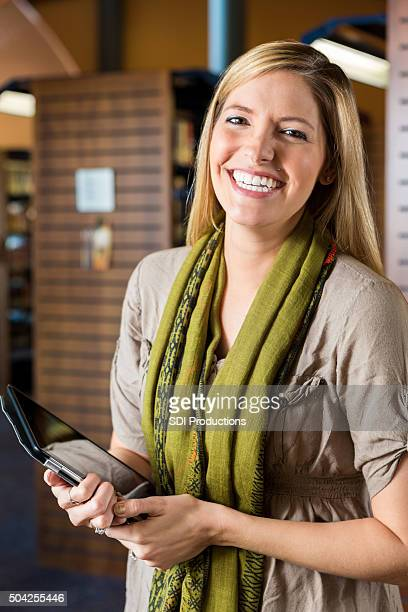 Happy library patron using digital tablet in public library