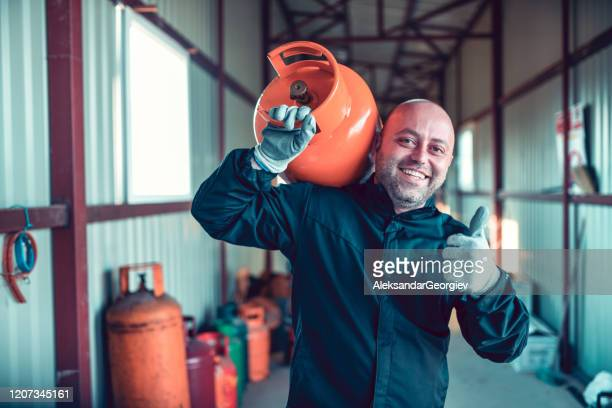 happy liquified gas storage worker carrying gas cylinder on shoulder - butane stock pictures, royalty-free photos & images