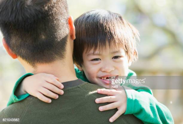 幸せのアジアの少年が父の肩越しに見ています。 - looking over shoulder ストックフォトと画像