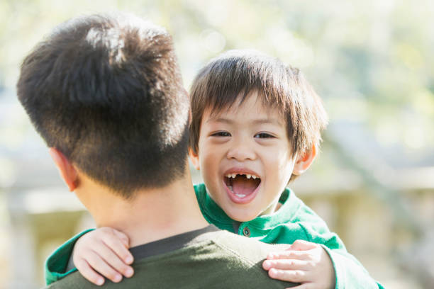 happy little asian boy looking over father's shoulder - asian father and little son stock pictures, royalty-free photos & images