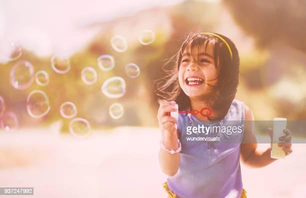 幸せのアジアの女の子が遊び場でシャボン玉を吹く