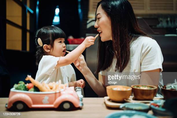 happy little asian girl enjoying her kids meal set with her mother in a restaurant. they are feeding each other with french fries and having a enjoyable time together - toddler stock pictures, royalty-free photos & images