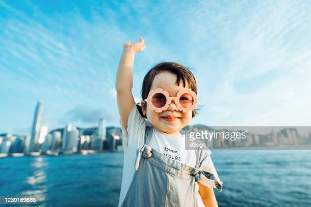 happy little asian girl with flower-shaped sunglasses smiling joyfully while having fun outdoors and imagines flying in the air against a clear blue sky and urban city skyline - hand raised stock pictures, royalty-free photos & images