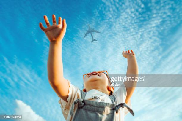 happy little asian girl with flower-shaped sunglasses smiling joyfully and raised her hands waving to the aeroplane in the clear blue sky - heaven stock pictures, royalty-free photos & images