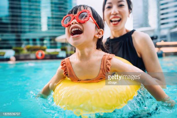 happy little asian girl with sunglasses smiling joyfully and enjoying family bonding time with mother, having fun in the swimming pool on summer vacations - purity stock pictures, royalty-free photos & images