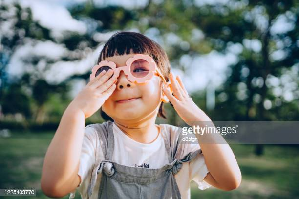 happy little asian toddler girl with flower-shaped sunglasses having fun outdoors enjoying summer days in the park - girls sunbathing stock pictures, royalty-free photos & images