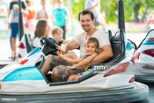 happy little boy and father in bumper car