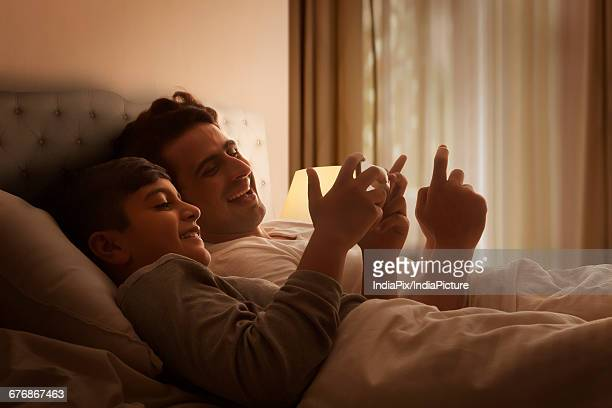 Happy little boy and his father using cell phone in bedroom