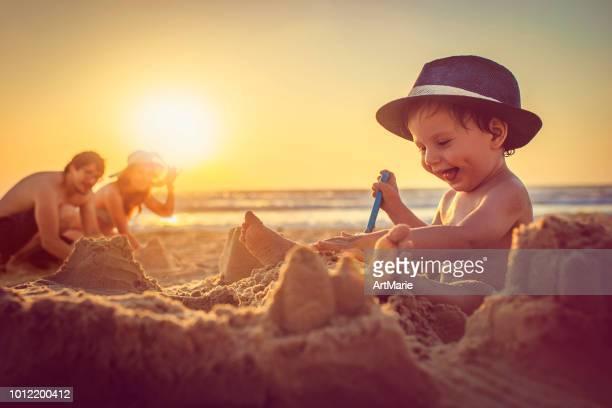 feliz niño construyendo castillos de arena en la playa - vacaciones de sol y playa fotografías e imágenes de stock