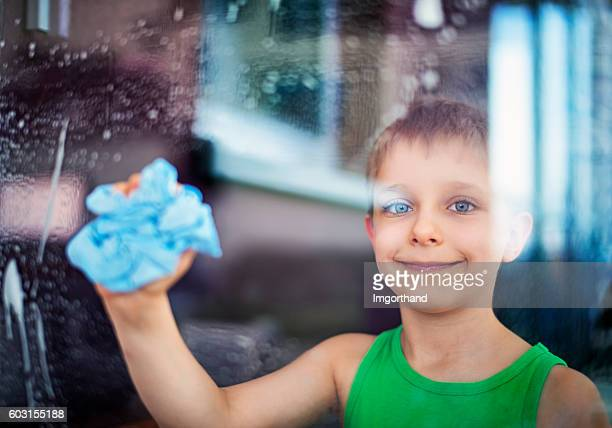 Happy little boy cleaning windows