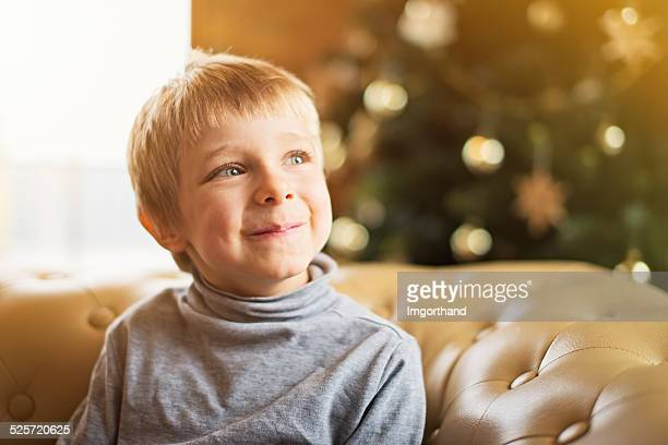 Happy little boy dreaming about christmas