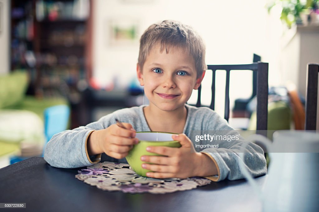 Felice piccolo ragazzo mangia Cereali da colazione : Foto stock